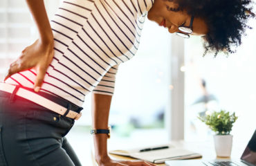young businesswoman holding her back in discomfort